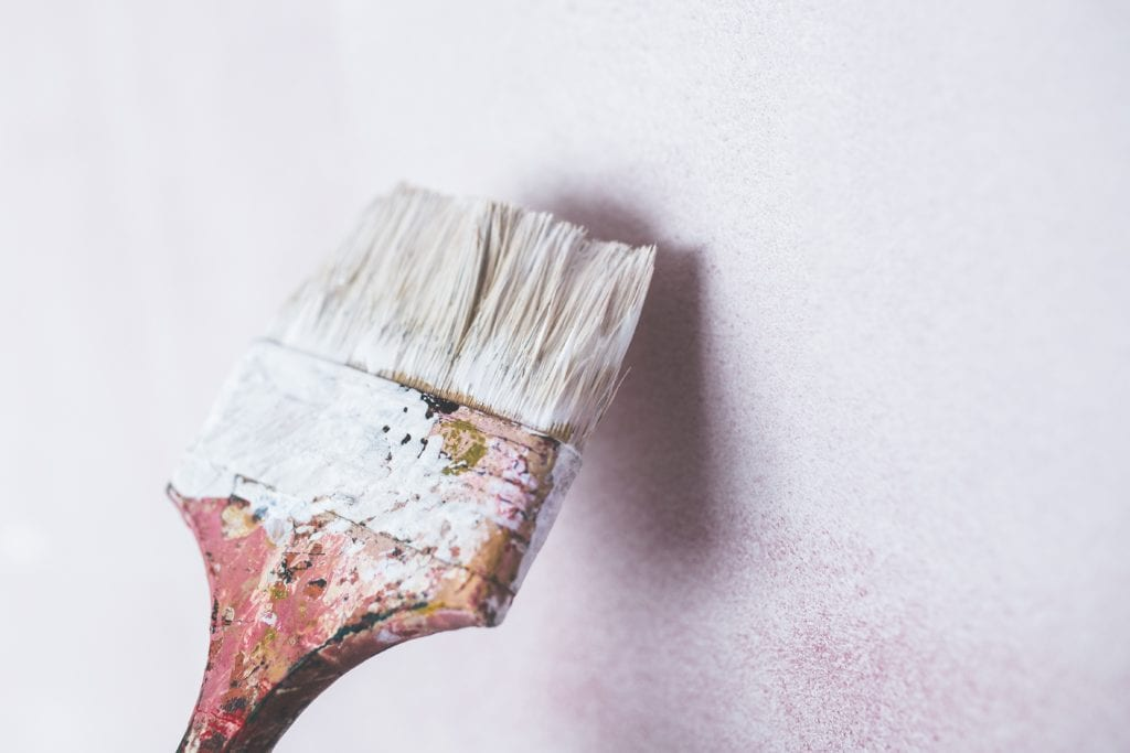 A person painting a wall white.