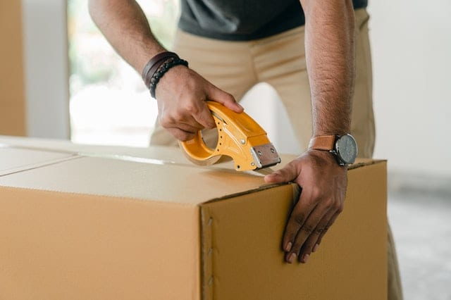 A mover taping a large box