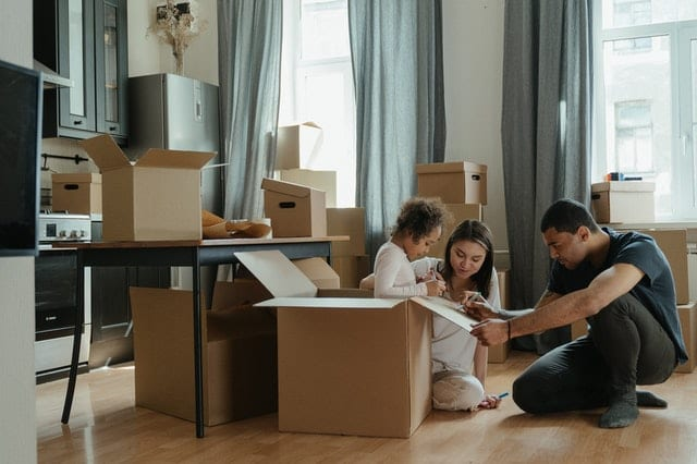 A family drawing on large moving boxes